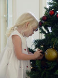 How does this work?. A little girl putting up the xmas decorations Stock Photo