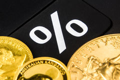 How many percent is gold going up or down.. Golden coins are laying on black percentage button stock photos