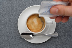 How many sugar?. Coffeecup with hand and sugar Royalty Free Stock Photography