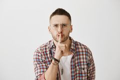 How many times I should tell to keep mouth shut. Angry displeased young man with beard in glasses bending towards camera. Squinting and making shh gesture with Royalty Free Stock Image