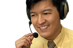How May I Help You?. Asian male adjusting headset while on the line with customer Stock Photography