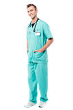 How may i help you ?. Full length of male doctor with hands in pockets stock image