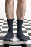 How much do I weigh. Man in socks standing on scale with on checkered floor Royalty Free Stock Photography
