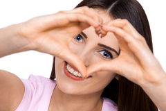 How much do you love me??. A cropped portrait of a beautiful young woman making a heart shape with her hands Royalty Free Stock Image