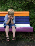 How Much Longer!. A little boy waiting on a park bench looking very bored Royalty Free Stock Image