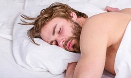 How much sleep you actually need. Man handsome guy lay in bed. Get adequate and consistent amount of sleep every night stock image