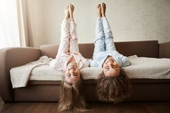 How nice to lie and fool around all day with girlfriend. Charming childish european women lying on sofa in nightwear. With lifted hands and head upside down Stock Photography