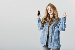 How people live without earphones. Indoor shot of satisfied cheerful young woman in denim jacket, dancing with raised. Hands, holding smartphone while listening Stock Image