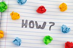 How question on notebook sheet with some colorful crumpled paper balls around it. How? How question on notebook sheet with some colorful crumpled paper balls royalty free stock photo