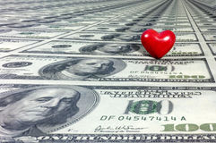 How sweet... A red heart on a sea of many one hundred dollar bills. With space for copy stock images