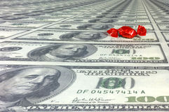 How sweet... A red wraped candy on a sea of one hundred dollar bills. With space for copy stock images