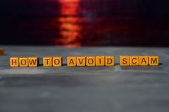How to avoid scam? on wooden blocks. Cross processed image with bokeh background stock image