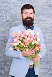 How to be gentleman. Guide for modern man. Romantic man with flowers. Romantic gift. Macho getting ready romantic date. Tulips for sweetheart. Man well groomed stock photography