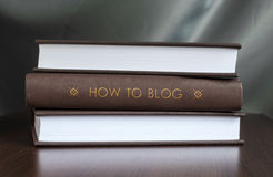 How to blog. Book concept. Books on a table and one with  how to blog  cover. Book concept Royalty Free Stock Photography