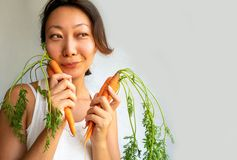 Pregnant asian woman holding bunch of carrots. royalty free stock photos