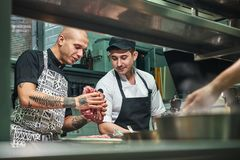 How to choose the right meat Professional chef in apron and with tattoos on his arms showing a red meat to his assistant. While standing in a restaurant kitchen stock photography