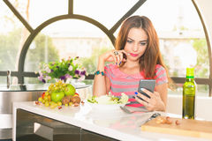 How to cook. Attractive girl cooking, looking recipe in internet Stock Photography