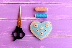 How to create a felt heart crafts. Step. Decorative felt heart with buttons, scissors, thread set, needle on wooden background Royalty Free Stock Photos