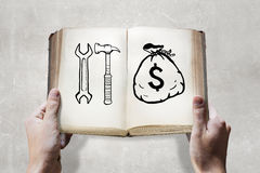 How to earn money. Opened book in male hands with financial ideas on pages Stock Image