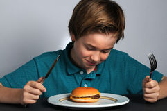 How to eat a hamburger Royalty Free Stock Image