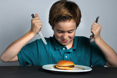 How to eat a hamburger. ? Helpless  boy with cheeseburger Royalty Free Stock Image