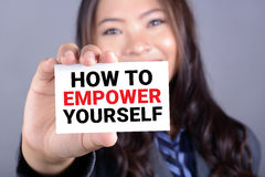 HOW TO EMPOWER YOURSELF message on the card shown by a businessw Stock Image