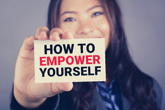 HOW TO EMPOWER YOURSELF message on the card shown by a businesswoman. Vintage tone effect royalty free stock photography