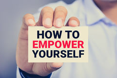 HOW TO EMPOWER YOURSELF message on the card shown by a man Royalty Free Stock Photos
