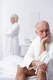 How to find the way to the end of the argument?. Sad old men is sitting on the bed when his offended wife looks out the window Royalty Free Stock Photo