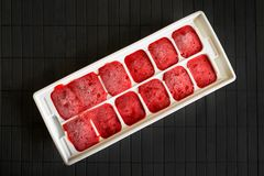 How to freeze strawberries. The strawberry puree is frozen in th. E form for ice. Homemade red popsicles with strawberry on a black wooden background. Top view Stock Images
