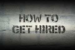 How to get hired gr. How to get hired stencil print on the grunge white brick wall Royalty Free Stock Photos