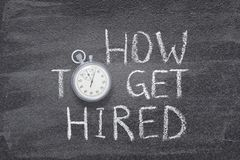 How to get hired watch. How to get hired phrase handwritten on chalkboard with vintage precise stopwatch used instead of O Royalty Free Stock Photo
