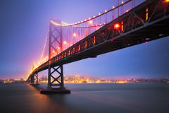 How to Get There, Bay Bridge, San Francisco. The Historic Bay Bridge in San Francisco, California illuminates the foggy dusk evening and the city comes alive Stock Images