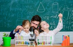 How to interest children study. Fascinating biology lesson. Man bearded teacher work with microscope and test tubes in. Biology classroom. School biology stock photos
