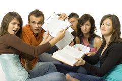 How to learn it?. Group of students sitting and showing open books to the camera. They're looking sad. White background Stock Photography