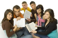 How to learn it?. Group of students sitting and showing open books to the camera. They're looking sad Stock Image