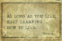 How to live Seneca. As long as you live, keep learning how to live - ancient Roman philosopher Seneca quote printed on grunge vintage cardboard Royalty Free Stock Image