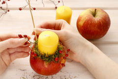 How to make apple and wild rose candle holders Royalty Free Stock Image