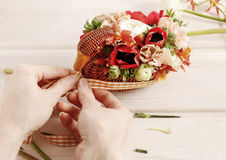 How to make bouquet of flowers in wicker goose. Stock Images