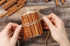 How to make candle decorated with cinnamon sticks tutorial Stock Images