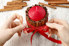 How to make candle decorated with cinnamon sticks - tutorial Stock Image
