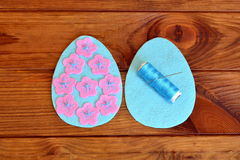 How to make a felt Easter egg. Sewing set Easter felt eggs. Felt details of egg, thread, needle on a brown wooden background Stock Photos