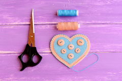 How to make a felt heart crafts. Step. Join the felt edges of felt heart with blue thread. Scissors, thread, needle Royalty Free Stock Images