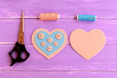How to make a felt heart crafts. Step. On one side of the felt heart buttons sewn using blue thread. Scissors, thread, needle Stock Photo