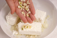 How to make homemade cottage cheese spread. One hand and some garlic Royalty Free Stock Photography