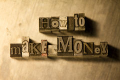 How to make money - Metal typography lettering sign. Lead metal  typography text on wooden background Stock Image