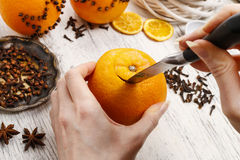 How to make orange pomander ball with candle - tutorial. How to make orange pomander ball with candle - step by step, tutorial stock image