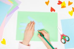 How to make paper bunny for Easter greetings and fun. Children art project. DIY concept. Kids hands makes paper craf. Step by step. Photo instruction. Step 4 stock image