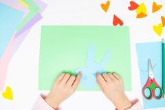 How to make paper bunny for Easter greetings and fun. Children art project. DIY concept. Kids hands makes paper craf. Step by step. Photo instruction. Step 6 royalty free stock image