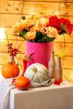 How to make a Thanksgiving centerpiece with big pumpkin and bouquet of flowers. royalty free stock image